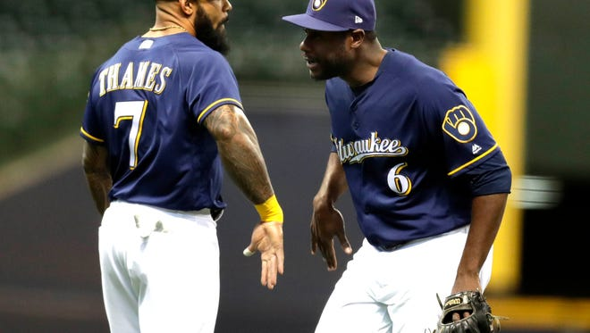 Eric Thames celebrates the Brewers' victory over the Reds with Lorenzo Cain on Wednesday.