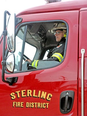 Assistant Fire Chief Josh Bischoff backs a fire truck into the station at the Sterling Fire District.