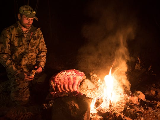 Remi Warren, 30, of Reno cooks over a campfire in this production photo from a televised hunting series on the Sportsman Channel.