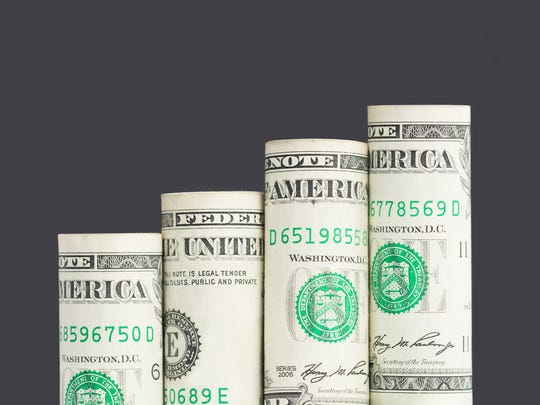 A series of rolled-up U.S. dollars stacked in a manner that appears to represent a positive trend.
