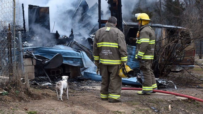 A dog and Oakland-Promise Land firefighters look over the charred remains of Perry Boore's home on Marion County Road 144 on Wednesday.