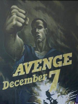 Ken Mullinax displays an original Avenge December 7 World War II poster on Monday November 30, 2015.