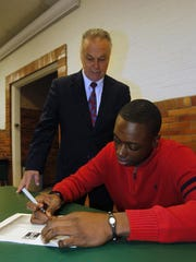 Jerry Smith looks on as basketball star Quenton DeCosey signs a National Letter of Intent to attend Temple University in 2011.