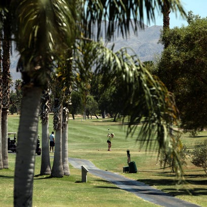 A golfer tees off at Desert Princess Country Club in