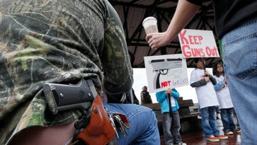 Greg Dement, left, is handed a cup of coffee as he sits March 3, 2015, with a handgun strapped to his belt while looking on at an anti-gun rally in Seattle.