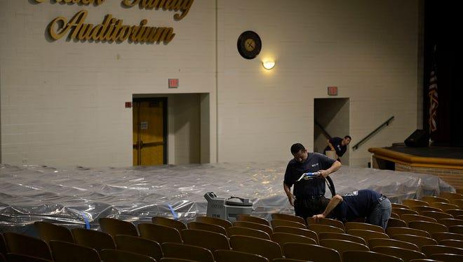 Crew members clean the seats inside the auditorium at Green Bay Preble High School last week.