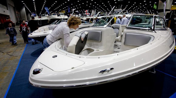 2010 file photo: Jennifer Pittelko, of New Albany, examines the storage room beneath a seat in a bow rider boat during the Louisville Boat, RV and Sportshow.