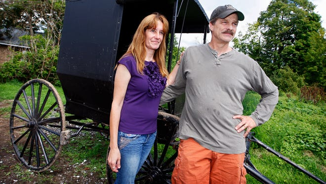 Jeffrey and Pamela Stinson pose for a portrait outside an Amish buggy on Aug. 23, 2014 in Bigelow, N.Y.