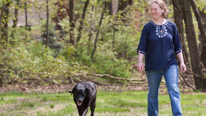Kelly Brown walks with her 11-year-old English Black Labrador Tyler in Bear on Friday.
