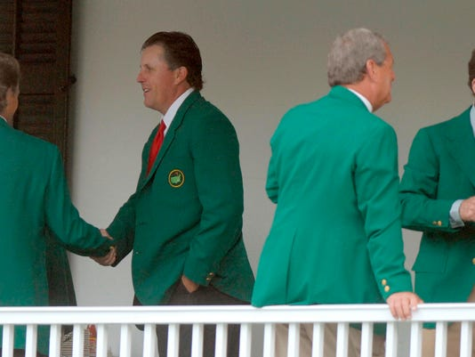 FILE - In this Tuesday, April 3, 2007, file photo, Phil Mickelson, second from left, shakes hands with Bernhard Langer of Germany during the Masters Champions Dinner at the Augusta National Golf Club in Augusta, Ga. Also pictured are past winners Tom Watson, far right, and Fuzzy Zoeller. The defending champion hosts the dinner. The rest of the past Masters champions have to figure out their own seat at the table.  (Chris Thelen/The Augusta Chronicle via AP, File)