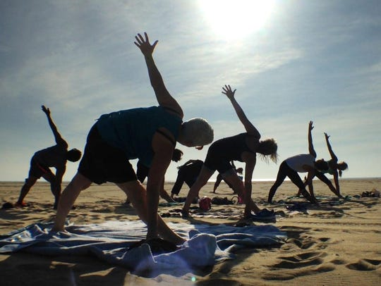 Patrons take advantage of free yoga on the beach by