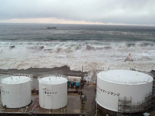 Waves from the tsunami come toward tanks of heavy oil for the Unit 5 of the Fukushima Dai-ichi nuclear complex in Okuma, Fukushima Prefecture, northeastern Japan.