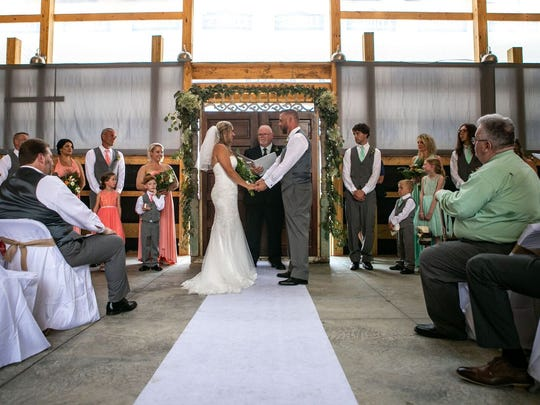 Bethany and Todd Snowden are seen exchanging their vows during their Saturday wedding in the barn that will become the Creekside Occasions wedding and events center sometime this fall. The couple has been hands-on with others in building the barn off Ohio 772 just south of town from scratch.