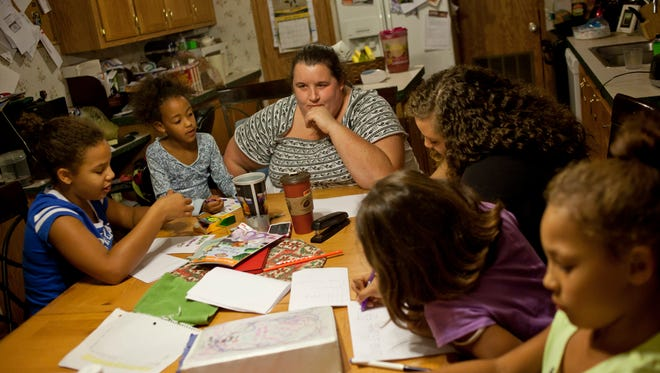 Joelle Graham sits with her children Kashanna, 12, left, Adryanna, 5, Shanna, 19, Allissa, 9, and Leah, 9, as they work on making Veterans Day cards for their grandfather Tuesday, November 10, 2015 at their home in Port Huron Township.