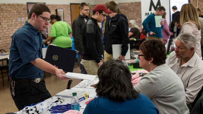 Alex Fladzinski, of Greenwood Township, hands his resume to representatives of MAPAL in Port Huron during a career fair Wednesday, April 20, 2016 at St. Clair County Community College in Port Huron.
