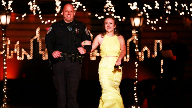 Everest Metro Officer Frank Wierzbanowski escorts junior Krystal Walls during the D.C. Everest High School Prom on Saturday, April 28, 2018.