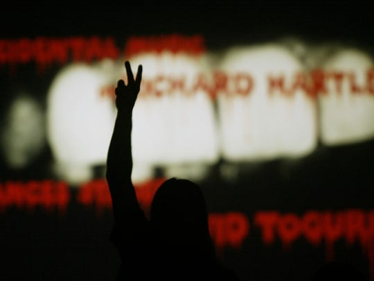 "A fan raises a peace sign during the opening credits of the ""Rocky Horror Picture Show."""