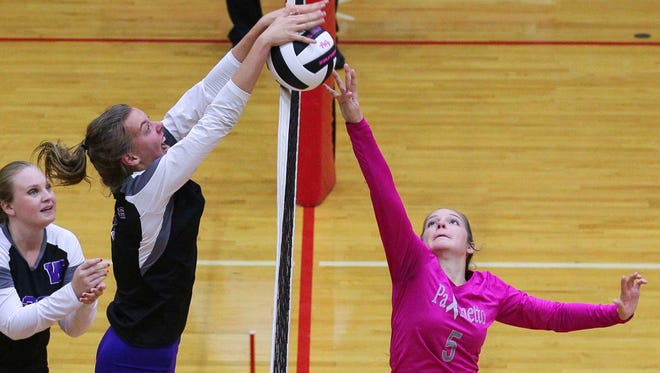 Walhalla freshman middle hitter Zoe Zimmerman (8), left, and Palmetto senior setter Jennifer Johnston battle for a ball at the net.