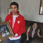 Jose Cabrera holds a family photo showing his two younger sisters, who are U.S. citizens. He and his mother Maria (sitting) are both undocumented immigrants.