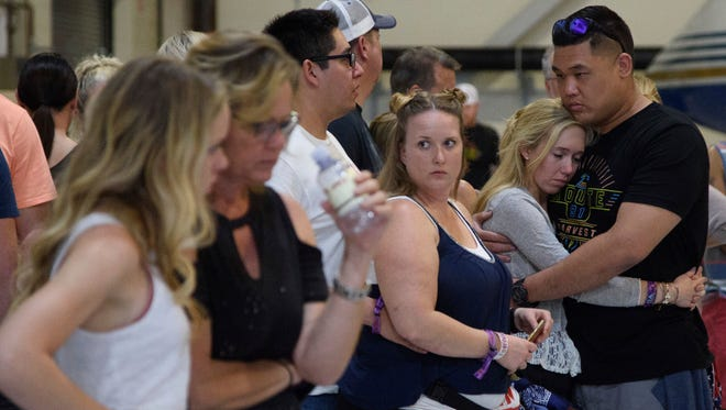 Concertgoers embrace as they wait early Monday, Oct. 2, 2017, inside the Sands Corporation plane hangar after a mass shooting in which dozens were killed  at the Route 91 Harvest country festival early Sunday.