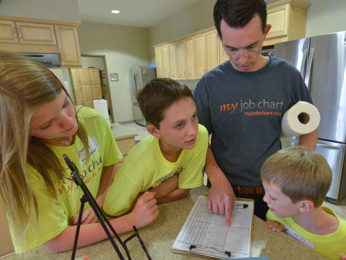 Gregg Murset and his kids Sydney, 13, Adam, 11, and Sterling, 7, checks the chores to do list while visiting the Ronald McDonald House Friday morning July 18, 204. The Murset family is spending their summer vacation traveling the county in a motorhome and doing chores for people in need in each community the family stops.