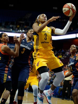 Indiana Fever's Tiffany Mitchell, center, breaks through the defense of Connecticut Sun's Jasmine Thomas, left, Kelsey Bone, center, and Camille Little, right, during the second half of a WNBA basketball game, Sunday, June 5, 2016, in Uncasville, Conn. Indiana won 88-77. Mitchell had 21 points for the Fever. (AP Photo/Jessica Hill)