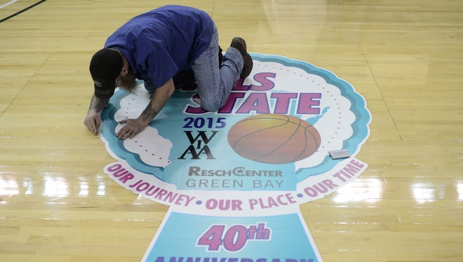 Josh Bevers of Fastsigns works on the edges of the floor decal for the 2015 WIAA girls state basketball tournament at the Resch Center in Ashwaubenon.