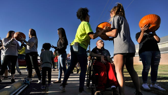 Abilene High School junior Brooklin Ellis (in green) hands a pumpkin to sophomore Calee Payne while the pair talk with Patrick Ludwig at Disability Resources Inc. Tuesday, Oct. 17, 2017. More than 100 local student/athletes volunteered to assist unloading an 18-wheeler full of pumpkins for DRI's annual pumpkin patch at 3602 N. Clack St. The pumpkin patch, a fundraiser for DRI, is open Mondays through Saturdays from 10 a.m. to 7 p.m. and Sundays from 1 to 7 p.m. Last year more than 71 tons of pumpkins were sold. More than 13,000 visitors and 70 school groups visited the patch, which is decorated with bales of hay, scarecrows, flowers, and, of course, pumpkins.