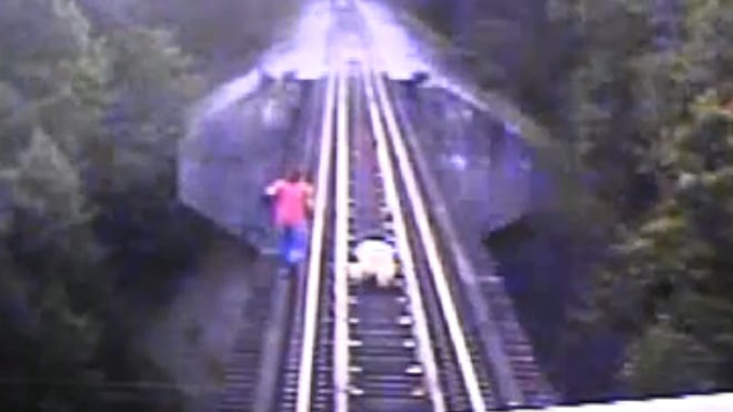 The two women barely avoided death by lying below a train between the rails as the train passed over.