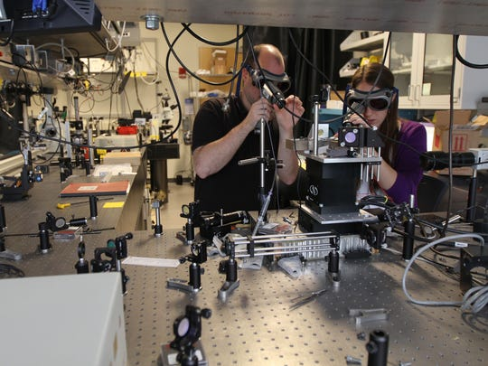 Daniel Brooks and Sara Gearhart, graduate students under Professor Wayne Knox of the University of Rochester, wear safety goggles and use special scopes to view an optical laser under development.