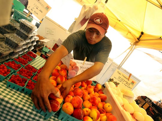 Edwin Velez from Vacchiano Farms fills cartons of peaches