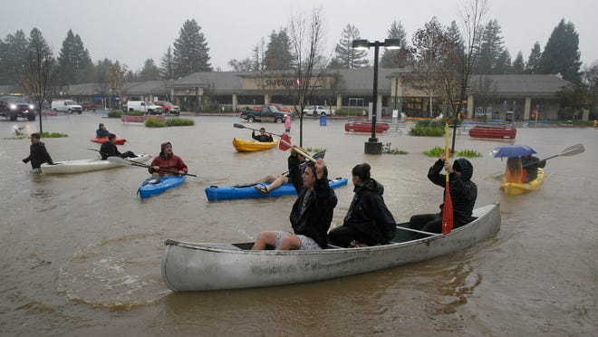 People use kayaks and a canoe to make their way around a flooded parking lot at a shopping center Thursday, Dec. 11, 2014, in Healdsburg, Calif. A powerful storm churned through Northern California Thursday, knocking out power to tens of thousands and delaying commuters while soaking the region with much-needed rain. (AP Photo/Eric Risberg)