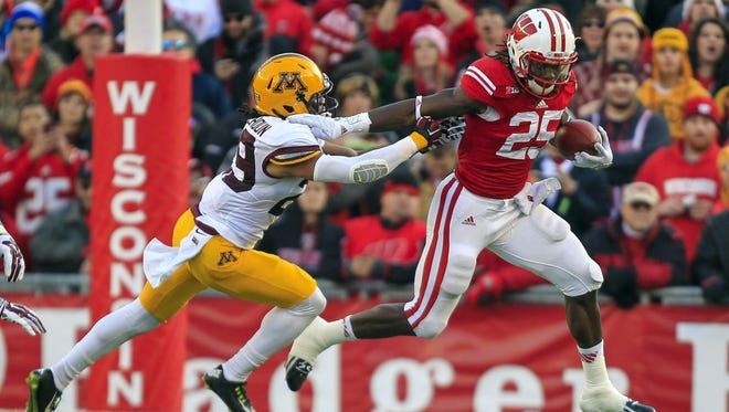 Wisconsin's Melvin Gordon (25) runs by Minnesota's Brien Boddy-Calhoun during the first half of Saturday's game in Madison.