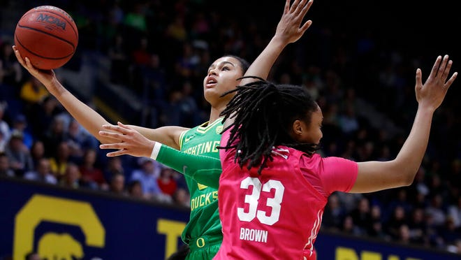 From Feb. 21, 2020, Oregon's Satou Sabally, left, shoots past California's Jaelyn Brown (33) in the first half of an NCAA college basketball game in Berkeley, Calif. The Associated Press had a panel of WNBA coaches and general managers hold a mock draft.