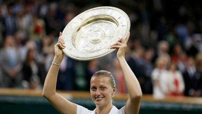 Petra Kvitova of Czech Republic holds up the winner's trophy, the Venus Rosewater Dish, after defeating Eugenie Bouchard of Canada in their women's singles final tennis match at the Wimbledon Tennis Championships in London July 5, 2014.