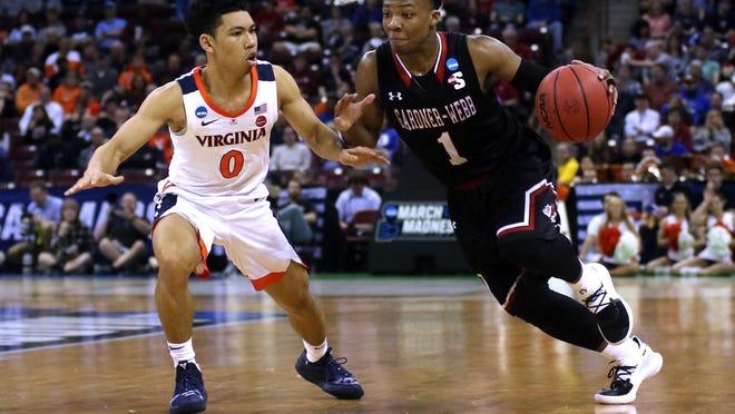 Jaheam Cornwall takes the ball around Virginia's Kihei Clark in the first-round NCAA tournament game. [AP FILE]