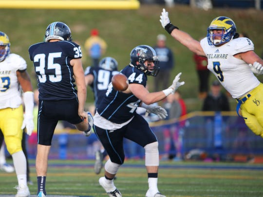 Delaware linebacker Troy Reeder leaps to block a punt by Maine's Derek Deoul in the third quarter of Delaware's 31-17 win in Portland, Maine last year.