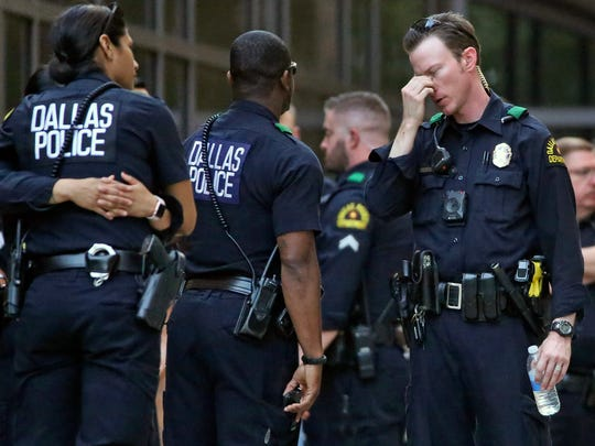 Dallas police officers wait outside the entrance of the emergency room at Presbyterian Hospital on April 24 in Dallas after a shooting at an area Home Depot in which two police officers and a civilian were shot. Officer Crystal Almeida, 26, was seriously wounded; Officer Rogelio Santander, 27, died the next day from his wounds.
