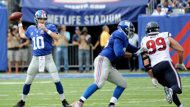 New York Giants quarterback Eli Manning (10) throws against the Houston Texans in the third quarter Sunday, Sept. 21, 2014, in East Rutherford, N.J.