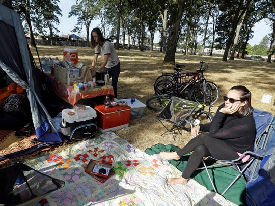 Hilary O'Hollaren, right, sits in the early morning sun as Rory O'Hollaren prepares breakfast as they camp near the state fairgrounds in preparation for the Aug. 21, 2017, solar eclipse in Salem, Ore., Sunday, Aug. 20, 2017.(AP Photo/Don Ryan)