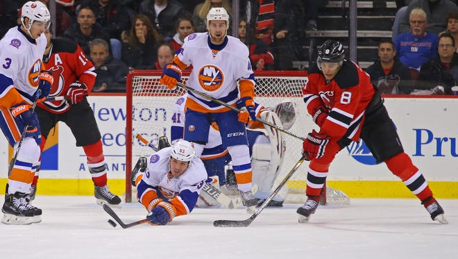 New York Islanders center Casey Cizikas (53) clears the puck in front of New Jersey Devils right wing Dainius Zubrus (8) during the third period at the Prudential Center.