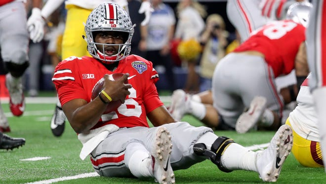 Ohio State Buckeyes quarterback J.T. Barrett (16) runs for a touchdown during the first quarter against the USC Trojans in the 2017 Cotton Bowl at AT&T Stadium.