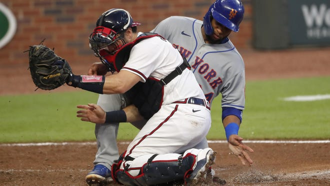 The New York Mets' Robinson Cano, rear, is tagged out at home plate by Atlanta Braves catcher Travis d'Arnaud as Cano tried to score on a J.D. Davis base hit during the fourth inning of a game Monday night in Atlanta. The Braves host the Toronto Blue Jays on Wednesday night.
