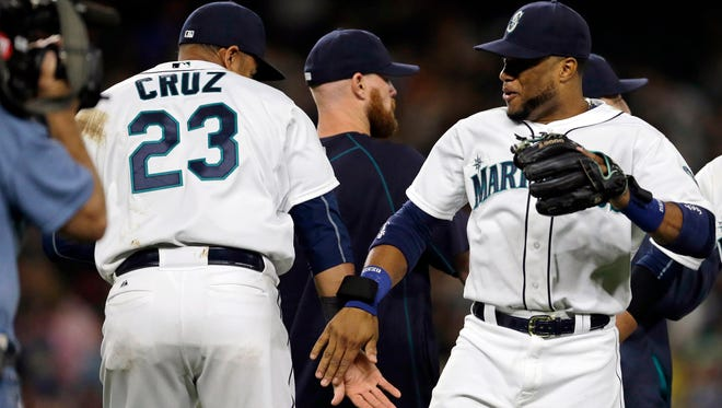 Seattle Mariners' Robinson Cano, right, slaps hands with teammate Nelson Cruz (23) after the Mariners beat the Colorado Rockies 7-2 in a baseball game, Saturday, Sept. 12, 2015, in Seattle.