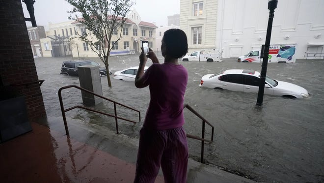 Flood waters move on the street Wednesday in downtown Pensacola, Fla.
