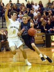 John Glenn's Justin Heacock drives into the lane against Tri-Valley's Keaton Williams during a regular season game in Dresden. Heacock will lead the Muskies into the Division II district semifinals on Wednesday.