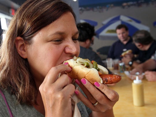 Jennifer Blackwell of Howell bites into a dog at Cioffi's Boardwalk in Union during the the 12th Annual Hot Dog Tour.