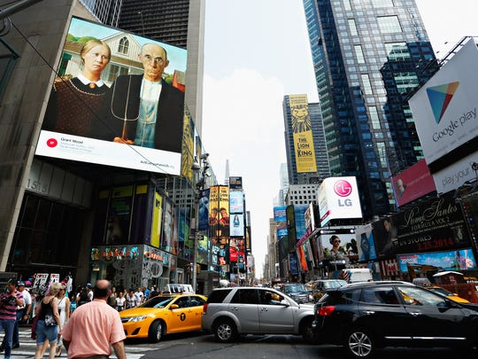 The image of 'American Gothic' by Grant Wood is seen on an electronic billboard on Aug. 4, 2014, in Times Square in New York.