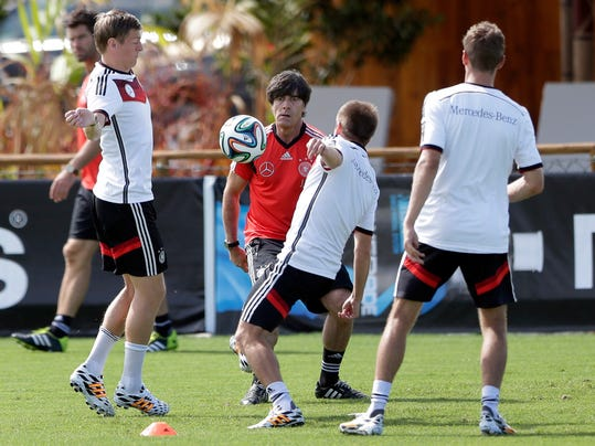 German national soccer team head coach Joachim Loew, background center, plays soccer with team members Toni Kroos, left, Philipp Lahm and Miroslav Klose during a training session in Santo Andre near Porto Seguro, Brazil, Saturday, June 14, 2014. Germany will play in group G of the 2014 soccer World Cup. (AP Photo/Matthias Schrader)
