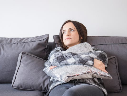 Depressed woman waiting with a pillow in her lap